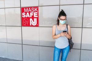 Woman in mask on her cell phone by a Mask Safe NJ sign