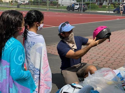 RideWise's Jon Dugan showing children how to pick out a helmet.