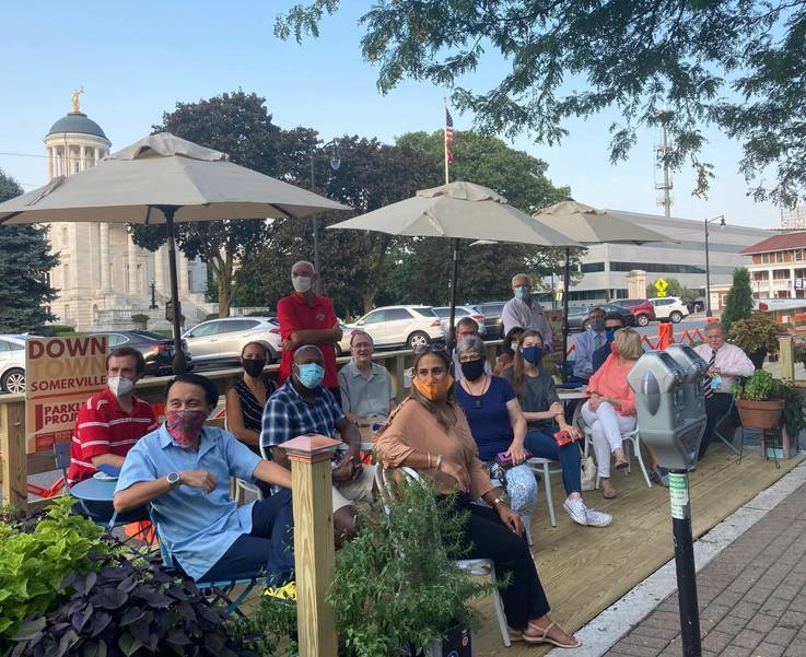 A group of people sitting in a parklet in Somerville.