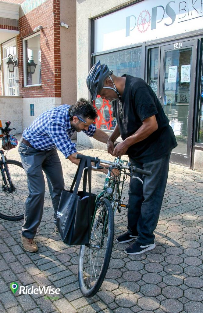 RideWise's Jon Dugan helps a BikeConnect client, Kevin, with adjusting his bicycle seat.